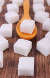 Wooden spoon with cubes of sugar on wooden background Stock Photo