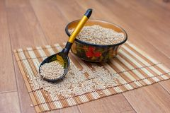 Wooden spoon and cup with pearl barley, Khokhloma. Wooden spoon and cup with the scattered pearl barley, Khokhloma Royalty Free Stock Photo