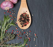 wooden spoon with different pepper, garlic, rosemary and herds Royalty Free Stock Image