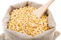 Wooden spoon in dried peas in sackcloth bag on white Stock Image