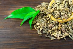 Wooden spoon of dry tea with green tea leaves on darkbackground stock image
