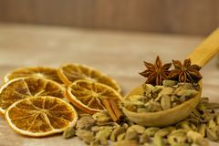 A wooden spoon filled with cardamom on the table next to dry oranges. stock image