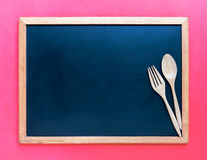 Wooden spoon and fork on blackboard. Use for background in kitch Stock Photos