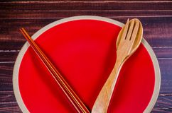 Wooden spoon and fork with chopstick in red plate on wooden tabl Royalty Free Stock Photo