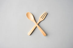 Wooden spoon and fork. Cross on grey paper background Royalty Free Stock Photography