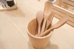 Wooden spoon and fork in a cup made of wood. Wooden spoon and fork in a cup made of wood in restaurant Royalty Free Stock Images