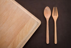 Wooden spoon and fork on cutting pad Stock Photo