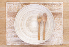 Wooden spoon and fork and empty wooden dish. Display on bamboo napery royalty free stock images