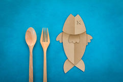 Wooden Spoon and fork with fish shape paper cut Royalty Free Stock Photo