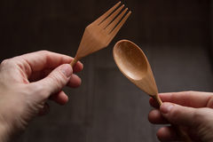 Wooden spoon and fork in the hands of women on dark background Royalty Free Stock Photo
