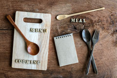 Wooden spoon and fork with note on old wooden textured Royalty Free Stock Images