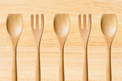 Wooden spoon and fork over wood texture close-up Royalty Free Stock Images