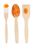 Wooden spoon, fork, paddle with dried apricots Royalty Free Stock Images