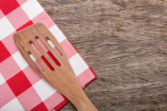 Wooden spoon, fork on red napkin for a table. Royalty Free Stock Photography