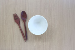 Wooden spoon,fork and white cup in top view on wood background. Wooden spoon,fork and white cup in top view on wood background for design concept food Stock Image