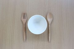 Wooden spoon,fork and white cup in top view on wood background. Wooden spoon,fork and white cup in top view on wood background for design concept food Stock Photography