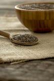 Wooden spoon full of chia seeds lying on burlap sac Stock Photo