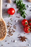 Spoon with coriander, cherry tomatoes, assorted spices on white background, flat lay, close-up, selective focus. Wooden spoon full of coriander, cherry tomatoes royalty free stock photography