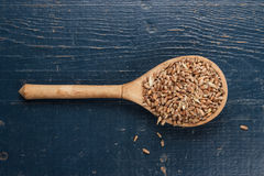 Wooden spoon full of crops on the blue table Royalty Free Stock Photography