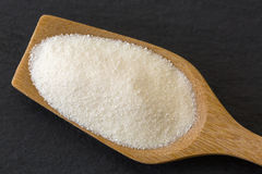 Wooden spoon full of dried white fine powder starch on dark ston Stock Photography