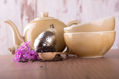 Wooden spoon full of dry tea and tea set Stock Photos