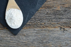 Wooden Spoon Full of Flour on Slate Cutting Board and Wood Backg Royalty Free Stock Photos