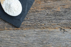 Wooden Spoon Full of Flour on Slate Cutting Board and Wood Backg Stock Photo