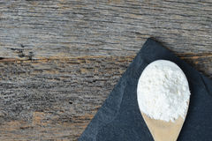 Wooden Spoon Full of Flour on Slate Cutting Board and Wood Backg Royalty Free Stock Photography