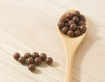 Wooden Spoon Full of Herbal Cough Lozenges on Cutting Board Royalty Free Stock Images