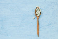 Wooden spoon full of pill Royalty Free Stock Photo