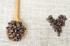 Wooden spoon full with roasted coffee beans and a coffee heart Stock Photos