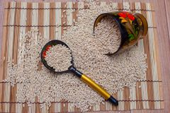 The wooden spoon and glass lie in the scattered pearl barley. The Russian Khokhloma Royalty Free Stock Photo