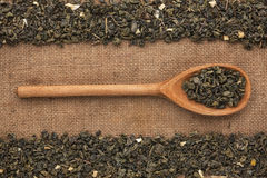 Wooden spoon with  green tea  lies on  sackcloth Stock Photography
