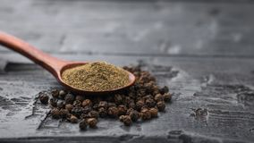 A wooden spoon with ground black pepper on a pile of whole pepper on a wooden table. royalty free stock photo