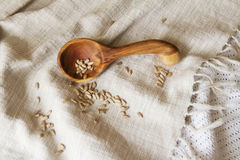 Wooden spoon hand on the table. Composition of wooden spoon on a drapery spilling seeds. Spoon from apricot wood Stock Photo