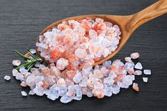 Wooden spoon with himalayan pink salt and rosemary on slate board background. With clipping path royalty free stock photo