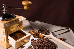 Wooden spoon holding coffee beans by grinder Stock Photography