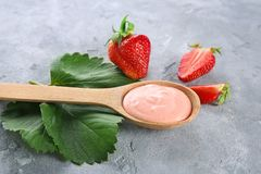 Wooden spoon of homemade yogurt with strawberries. On grey background Royalty Free Stock Photography