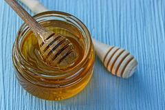 A wooden spoon in a jar with honey on the table Royalty Free Stock Photography