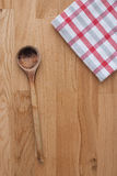 Wooden spoon and kitchen towel. On wooden background Royalty Free Stock Images