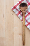 Wooden spoon and kitchen towel. On wooden background Stock Image