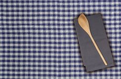 Wooden spoon and kitchen towel on blue white checkered kitchen t. Owel Royalty Free Stock Images