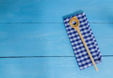 Wooden spoon and kitchen towel on blue wooden background Stock Photo