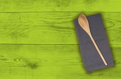 Wooden spoon and kitchen towel on green wood Stock Photo