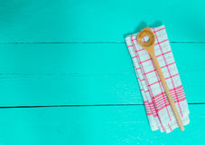Wooden spoon and kitchen towel on turquoise wooden background Royalty Free Stock Photography
