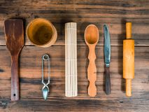 Wooden spoon, knife, rolling pin, turk for coffee, wooden mug and custard spoon for tea laid out on the table. Set of Stock Photography