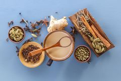 Wooden spoon lies on a mug of Masala tea on a background of spices of cinnamon, cardamom, ginger, clove, tuba, sweet pepper. View from above. Close-up royalty free stock photography