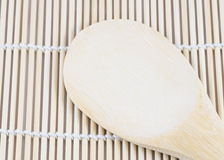 Wooden spoon on the making sushi bamboo mat Stock Photo