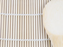 Wooden spoon on the making sushi bamboo mat Royalty Free Stock Photo
