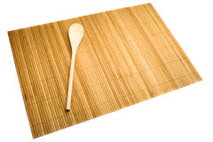 Wooden spoon on mat of bamboo Stock Photo